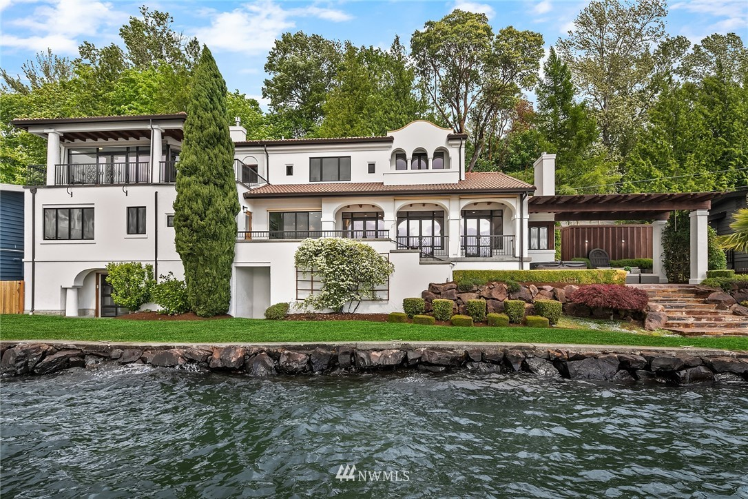 Reimagined by designer Diane Rosellini, paradise awaits on 105 ft of waterfront. Tuscan villa-style home features soaring ceilings & large windows. New hardwood leads into great room with water views. Chef's kitchen remodel features new quartz counters, Carrara backsplash & high-end Stainless appliances. Redesigned primary suite features private balcony, new 2nd walk-in closet, new porcelain floors, soaking tub & steam shower. Lake level features a kitchenette, game room, wine cellar, & private theatre. Landscaped yard leads to extended dock with deep water moorage and boat lift. Covered patio with hot tub provides  front-row seat to sunset views . Steps from Seahawks training facility and more. 2 car garage plus parking for multiple cars.