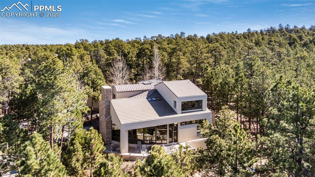 Situated at the end of a cul-de-sac, surrounded by 2.5 acres of Ponderosa pines and stunning views of Pikes Peak, this
