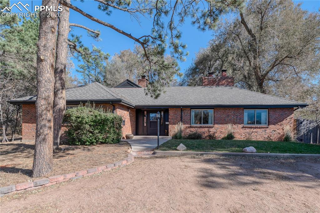 A rare opportunity to own this one-of-a-kind ranch home filled with charm and character in the historic Old North End of Colorado Springs. This lovely home with striking Pikes Peak views is centrally located but provides a secluded, peaceful feel with only one direct neighbor to the south behind the fence. Adjacency to Monument Creek and uninhabited property owned by Colorado College makes for a very peaceful existence, and the trail in front of the house allows you to walk/run/bike north or south along Monument Valley Park. Step through an incredible 100-year old Dutch door to a brilliant open floor plan filled with original dark-stained hardwood floors, beamed ceilings, exposed brick walls, 2 cozy fireplaces, and great natural light. The open floor plan between the entry foyer, kitchen, living area, office nook, and outdoor back patio flow seamlessly together - an ideal haven for entertaining. The kitchen and living room feature custom Bowers & Wilkins speakers that are pre-wired to the living area for a full surround sound home theater experience if desired. The kitchen and dining room is sure to delight boasting original wood cabinets (painted), beautiful gas-burning fireplace surrounded by a brick wall with a built-in oven, a center island 5-burner gas range with stainless overhead hood. Delightful nook with bump-out window behind the living room's fireplace makes a great little home office. Two spacious bedrooms including the primary bedroom with a dreamy spa-inspired en-suite bath featuring dual vessel sinks and an incredible over-sized double seamless shower. Attic contains 800' of unfinished space with 8' ceilings that could be converted into additional living space. Gorgeous park-like backyard with a newer custom cedar fence, a custom wrought iron fence over 120 years old from Hassle Iron Works, and 2 large Tuff sheds. Plenty of secluded parking and area frequented by CC security. Great location with CC across the street and downtown 1 mile away!
