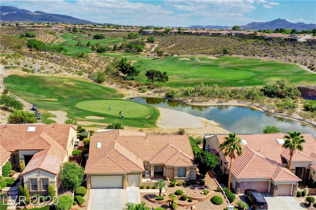 Arlington Sitting on Revere Golf Course in 55+Sun City Anthem, this outstanding home has views of greens, fairways & a pond that you will ask yourself if this is really the desert? 2321 SF, single-story home that offers spacious living with 3 BR, 2.5 baths, FR, LR, office space & 3 car gar. w/ one for golf cart. Mature multi-level landscaped front yd. & courtyard entry. Open LR & dining area w/ custom BI seating. Oversized window-lined family rm w/ FPL, BI, wet bar, wine fridge & slider to patio. Spacious kitchen, breakfast bar, granite counters, BI fridge, wall oven & gas stove top all overlooking the GC. Shutters & crown molding in every rm, tile floors except for 1 BR. Split BR floorplan. Rear Yd has breathtaking views of GC & rare to find-your own IG pool & spa. B/I BBQ for entertaining and 2 patios for quiet time. Rolladen shutters on some west windows for energy conservation. New HW htr.2020 & AC in 2016. Premium lot, outstanding views, fantastic home! SEE 3D TOUR