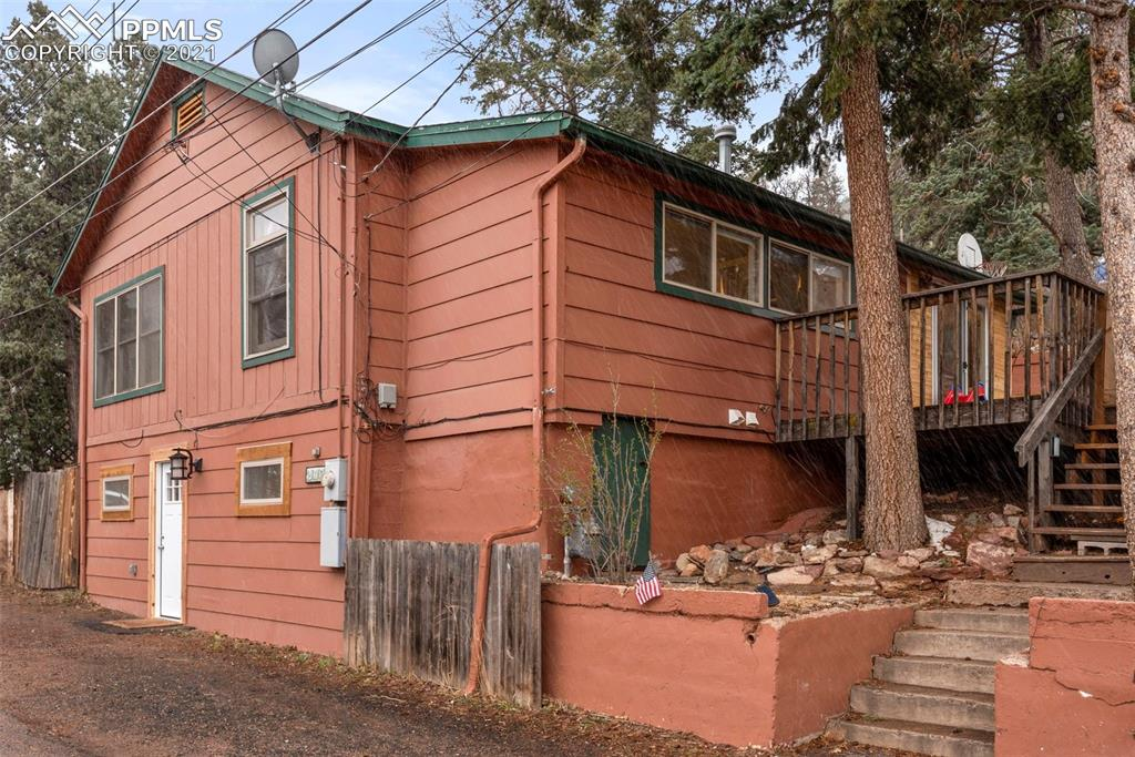 Your Manitou mountain retreat awaits! Quiet street within easy walking distance to hiking trails and downtown Manitou Avenue shops, restaurants, spa, and other amenities. Enter from the wood deck, and enjoy the privacy of mature fir trees that surround the big patio and large terraced yard (featuring a garden space with an arbor and irrigation watering line) with gorgeous views of Williams Canyon and Mt. Manitou. Come through the brand new sliding doors into the eat-in galley kitchen with ceramic tile floors, live edge pine countertops, and a full wall of windows that look into the backyard. Wonderful cross-breeze from the west facing sliding doors in the spring and summer. Head into the family room with hardwood floors and a freestanding wood burning stove. The two main level bedrooms with rebuilt custom closets are just off the family room. Main level bathroom features a jetted tub. Head downstairs to a second living area, third bedroom, full bath, and laundry area. You can walk out to the street from the lower level. Freshly painted! New water heater in 2017. New washer/dryer, carpets, and windows on lower level in 2019. New range oven in 2020. Furnace was serviced in February 2021. Glass doors have been installed on upper kitchen cabinets.