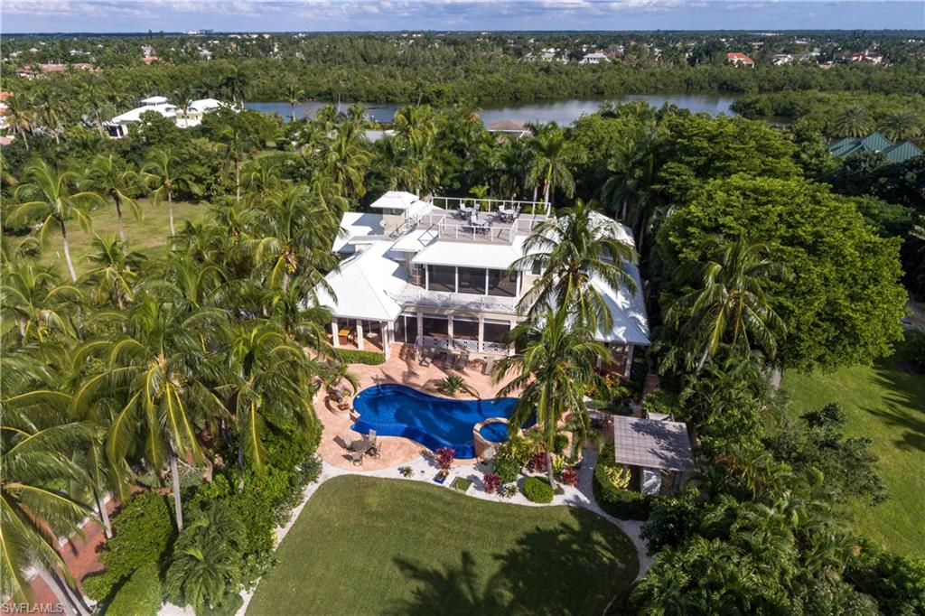 A Caribbean styled family home directly across from a private deeded beach access offering views of the Gulf of Mexico fringed by swaying palms. This refreshing luxury home was designed by Kasimir Korybut and built to the exacting standards of A. Vernon Allen Builders. Updated in 2014 by Paragon with a clean sophistication and a distinguished original style that sprawls over 7,855 square feet of living space featuring 4 bedroom suites, study, formal living room, dining room, home theatre and a gourmet styled kitchen. Additional features include wood and marble floors, fireplace, elevator, 8-car air conditioned garage, 80 kw whole house generator, and an abundance of storage space. The master suite, complete with his and hers baths, includes a spacious covered terrace with outstanding Gulf views. Perfect for al fresco dining, there is large covered porch the overlooks the vanishing edge pool and spa finished with mosaic glass tile and marble decking. This beautiful property has Port Royal membership eligibility.