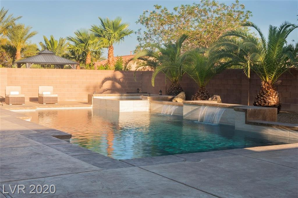 This beauty is situated in a gated community in the heart of Aliante. Home features a 100k resort style backyard which includes a refreshing pool w/ waterfalls, Jacuzzi, lush palm trees, gazebo, and upgraded stamped concrete.The interior is nicely appointed. Kitchen boasts an over-size granite island, adequate cabinet space, and SS appliances. Bed and full bath downstairs. The spacious Master bedroom includes large bathroom with his & hers sink, roman tub, and walk-in closet. OWNED solar panels installed last year! There are far too many features to list. Move-in ready!
