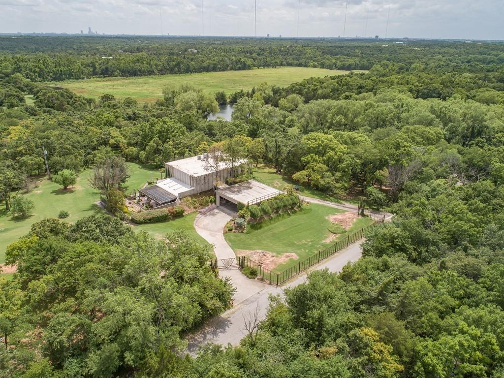 ONE OF A KIND FORTRESS!!! One owner custom home designed and owned by Lyle Cunningham one of OKC's designer legends! Gorgeous wooded lot on 4.08 acres mol! 75 X 40 building w/full apartment (bedroom, walk-in closet, 1.5 baths, kitchen, living room & utility room, shop area & 6 car garage. Total electric home w/well for house, building & sprinkler. 2 septic systems. Home was piered at construction. Stunning living room w/24 foot ceilings w/wall of windows floor to ceiling for maximum view, fireplace & bar. 2 master bedrooms-1 up & 1 down. Master down w/walk-in, full bath w/tub & moc fireplace. 2nd bed down w/full bath. 2nd master bed up w/balcony, wood burning fireplace, huge walk-in, full bath w/large whirlpool tub, custom etched glass w/peacocks, shower, 2 sinks & skylight. Kitchen w/built-in Kitchen Air fridge, breakfast bar & walk-in pantry. Den off kitchen w/skylight & vaulted ceiling. Loft area upstairs makes great home office or flex room. Peaceful country living at it's best!