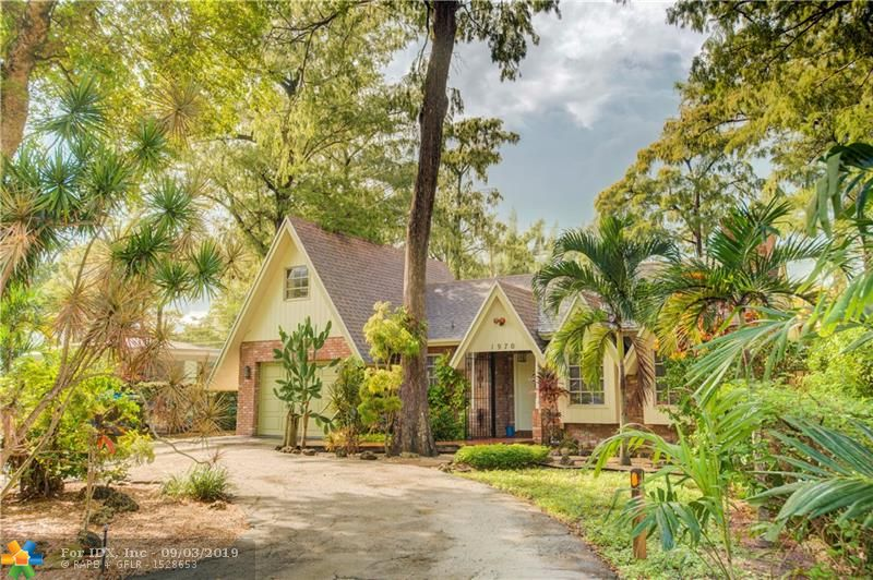 Unique Mountain Home in Tamarac Forest.  Rare opportunity to own a piece of a bygone era of detail and wood craftsmanship. This Oakland Park home warmly welcomes you with high-vaulted ceilings, exquisite wood detail, spacious floor plan, skylights, and a working fireplace. Complete with updated kitchen and bathrooms, specialized lighting, extra-large closets, bonus family room, outdoor covered patio, custom-built shed and more. Upstairs loft with closet and natural light is perfect for use as a 4th bedroom, office or even as a rental opportunity. The garage comes with custom built-in cabinets and workbench. Surrounded by beautiful trees, you are sure to love the peaceful tranquility of this home in the forest and forget you are just a few miles away from the beaches of Fort Lauderdale.