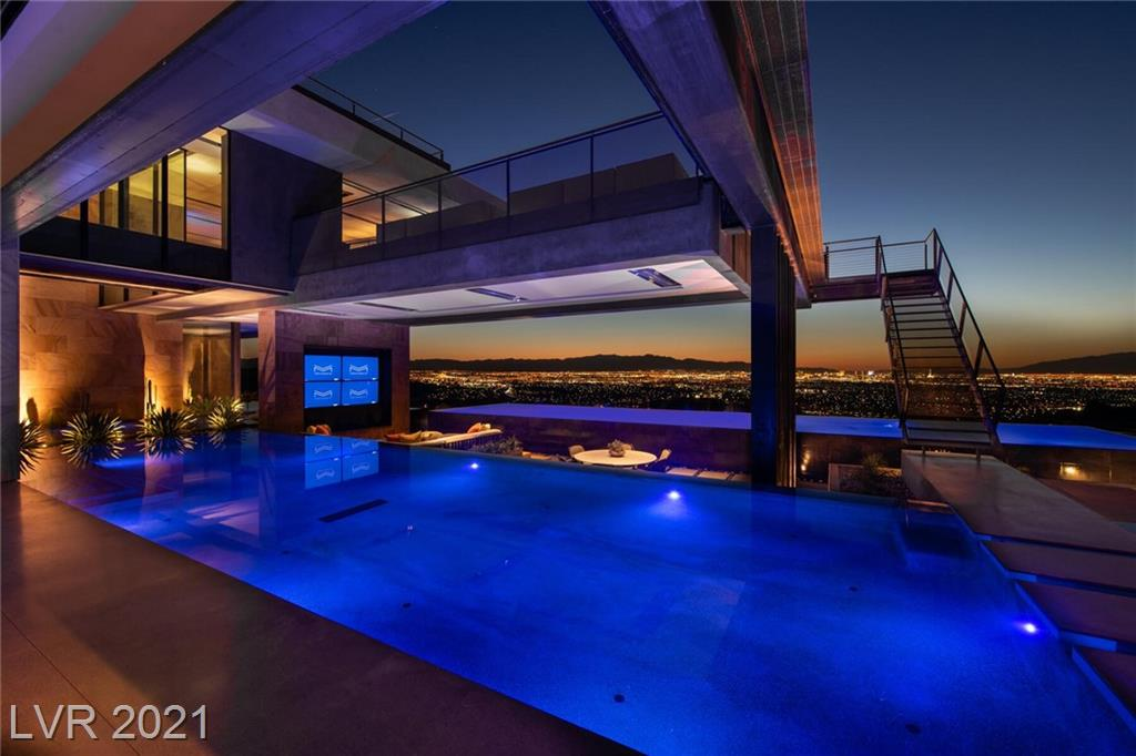 Vegas Modern 001. A Blue Heron Design-Build Revolution. An Experience that Unfolds in Layers, Speaking to You in a Personal Way. 15,000 SF | 3-7 Bed | 9 Bath | 5-11 Car | 1.26 Acres | 2 Infinity Saltwater Pools, 1 Spa, Glass Wine Cellar/Wall, Great Room Surrounded by Water, Game Lounge Loft, Pavilion Inspired Office/Casita, Sky Suite, Sky Lounge & Deck with 360 Panoramic Views. DJ Booth. Strip View Master. Spa Bath. His and Her Custom Closets. Private Outdoor Environment, Wolf /Subzero Chef Kitchen, Catering Kitchen, Outdoor Kitchen & Bar, 7 Fire Features, Digital Den. 13.5 ft LED Media Wall, Powder Bath with 35 ft. Ceiling, Covered Outdoor Living Room between two pools with Seamless Breezeways & Outdoor access from every room, Automatic Pocket & Corner Doors. Elevator, Stunning Strip, Mountain & City Views. Savant Smart Home Technology, Surround Sound & Security. Racepoint Solar Technology. Double Gated Dragon's Reserve Location. Experiences created by Design | Vision by Tyler Jones.