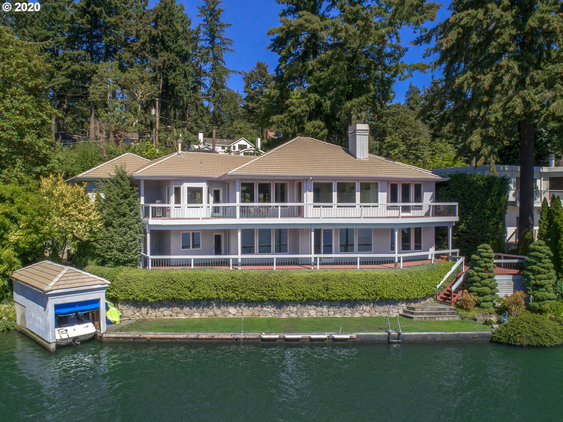 Custom built & boasting panoramic Oswego Lake views, private dock, boat house, walls of water-view windows & multi-level decks to take in the best of waterfront life. Relax & create your perfect, private world w/expansive great room & dining, kitchen w/wet bar & 2nd dining, main level master suite, lower level family rm, bedrooms & lake-view office. Lrg utility, extra storage, classic details & exclusive destination swimming/boat/water sports dock just minutes from vibrant downtown amenities!