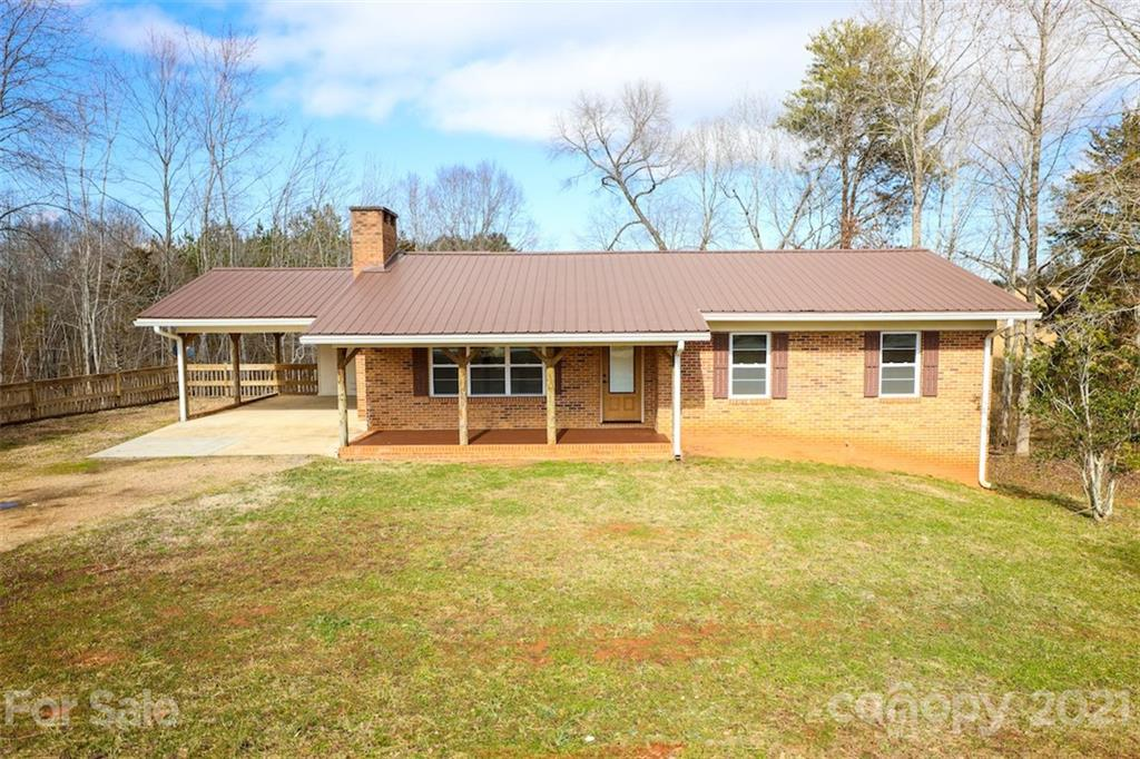 You need to see this updated, full brick home! Gleaming wood floors and lots of light welcome you to the open kitchen, dining, and living spaces.  The kitchen has plenty of cabinetry with an island, stainless steel appliances, and granite counters.  A deck is located just off the dining area which is perfect for grilling, and a covered front porch for rocking.  Two bedrooms, two full baths, and laundry complete the main level.  There is a door leading to the unfinished basement where additional rooms have been framed-in and ready to be completed. There is so much potential to be unlocked in this space! Situated on just under an acre and surrounded by fields with a distant mountain view. Come take a peek at this great home!