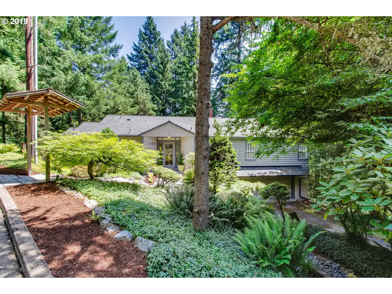 Over $50K invested since last on the market! Rare opportunity to be minutes from downtown yet in a peaceful forest. Move-in ready, master bed/bath on the main level, plus another bed & bath, formal dining or 4th bedroom, gourmet kitchen w/stainless top grade appliances, & huge living room & library/formal dining, big deck.  Another bedroom down w/ensuite bath, big family room w/fireplace, laundry plus tons of storage, 4th utility bath. Easy to add ADU. [Home Energy Score = 5. HES Report at https://rpt.greenbuildingregistry.com/hes/OR10118358]
