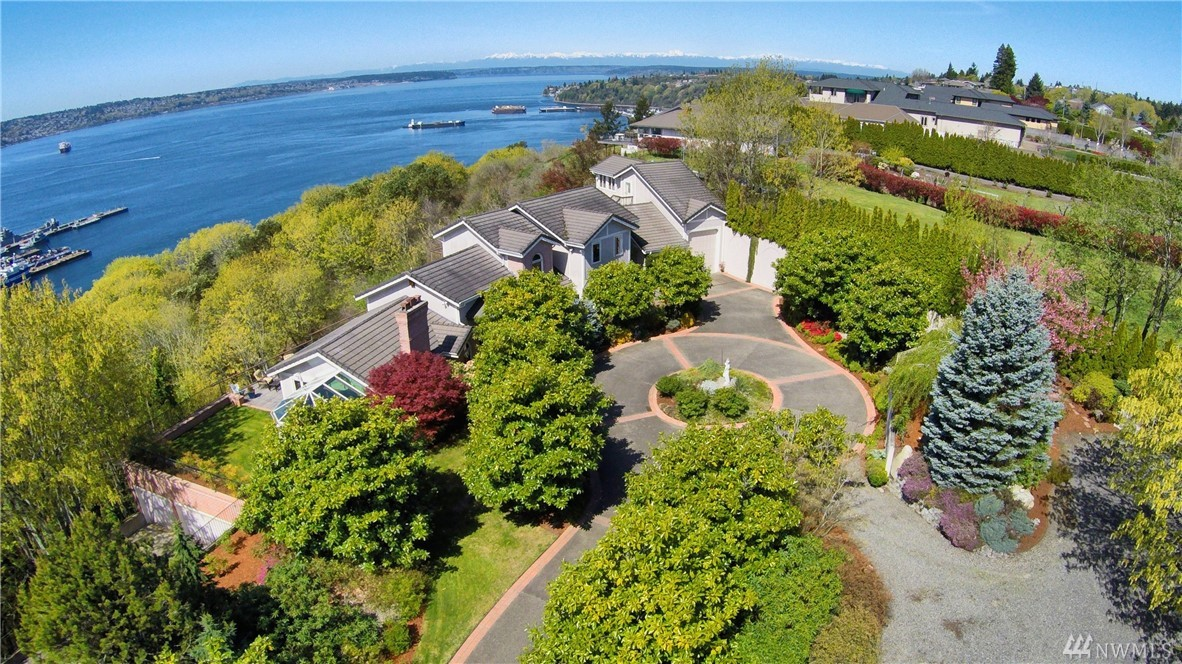 Stunning estate with views from Mt. Rainier to the Olympics on nearly 6 private acres high on the bluff of NE Tacoma. This elegant 4,300 sq ft one owner custom home is built with views from every room, a detached view apartment & garages for 6 vehicles - including one full length RV/boat bay w shop! Southern exposure fills the home with natural light, all the bedrooms have ensuite baths, multiple decks to entertain & a solarium by the living room to enjoy the sun all year. A remarkable home!