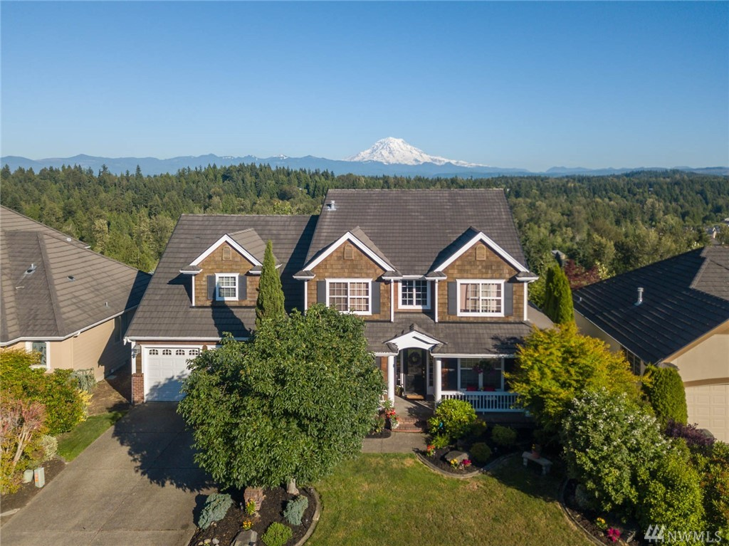 Custom, quality Zetterburg built home in highly sought after gated Sky Island community. Spectacular Mt. Rainier views from almost every room. Exceptional attention to detail thru-out. Enjoy coffee on the wrap-around porch or cocktails on one of 2 upper decks with views of the Cascade Mtns & Mt. Rainier. Spacious rooms. Gorgeous hardwood floors, butler's pantry, floor to ceiling stone fireplace, French doors, new carpet & paint, fireplace in master.  Enjoy the separate exercise room w/ sauna.