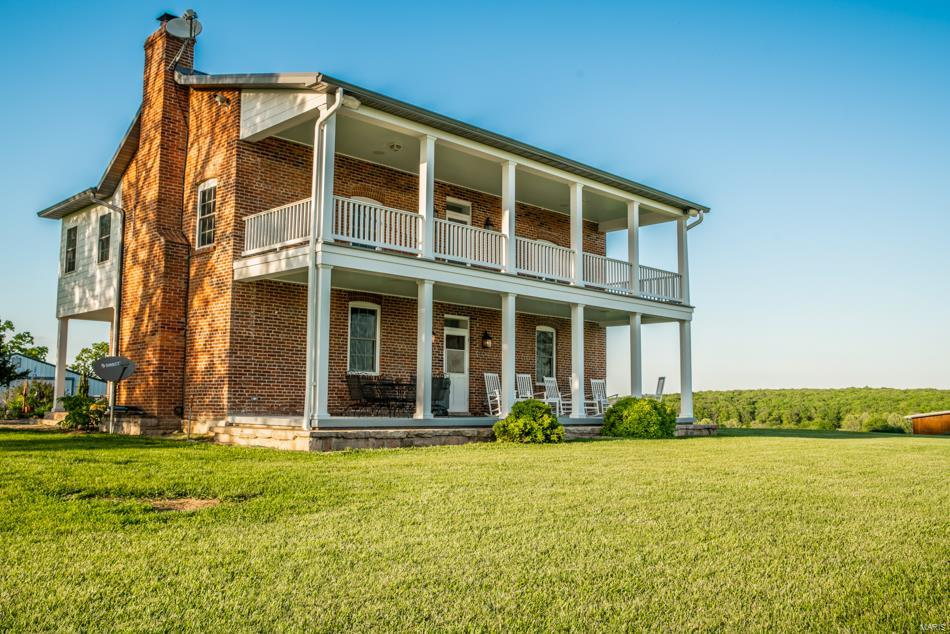 This modernized and recently renovated 1850's brick farmhouse sits on 111+ lush acres with two man-made lakes and a hand-built barn and stables. New kitchen with custom crafted cabinets and granite counters. The kitchen opens to a recreation area with a fireplace. The double front porch of the home creates a gracious exterior while providing a perch to view the fields and rolling hills that lead to a meandering creek. Main floor master bedroom suite. Upstairs are three bedrooms, a recreation room with bar and two full baths. Full unfinished basement. Windmill helps lower electric costs. Schedule your showing today to experience the feeling and lifestyle this historic farmhouse brings. Utility shed and caretaker's residence.