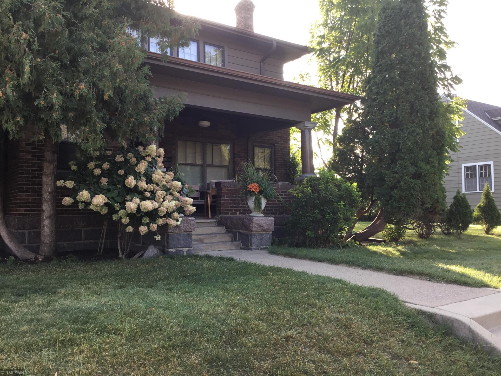 """This Historic Prairie Style two story home was built in 1917, and is still owned & lovingly maintained by the original family. It has 4+ bedrooms, 3 baths, 2 offices, Lg. FR, formal dining, an efficient and charming eat in kitchen with lots of cupboards and counter space,  9 ft ceilings. Bright and cheerful bedrooms.  9"""" oak baseboards, heavy oak trim, solid oak doors. The main floor living room """"decorative"""" fireplace and solid narrow maple flooring throughout. The basement has high ceilings with beautiful open unfinished joists,  3/4 bath,11x11 office, laundry with large folding counter, fruit cellar and wine cellar. The big yard has a perfect family location across from Lake George Municipal Complex & Clark Field.  It's walking distance to downtown and SCSU. Granite pillars, foundation & steps, brick and cedar siding exterior. The 2 car garage is granite and brick, and a unique granite wall next to garage,""""Old World""""perfect for today's world! Includes license mother-in-law apartment."""