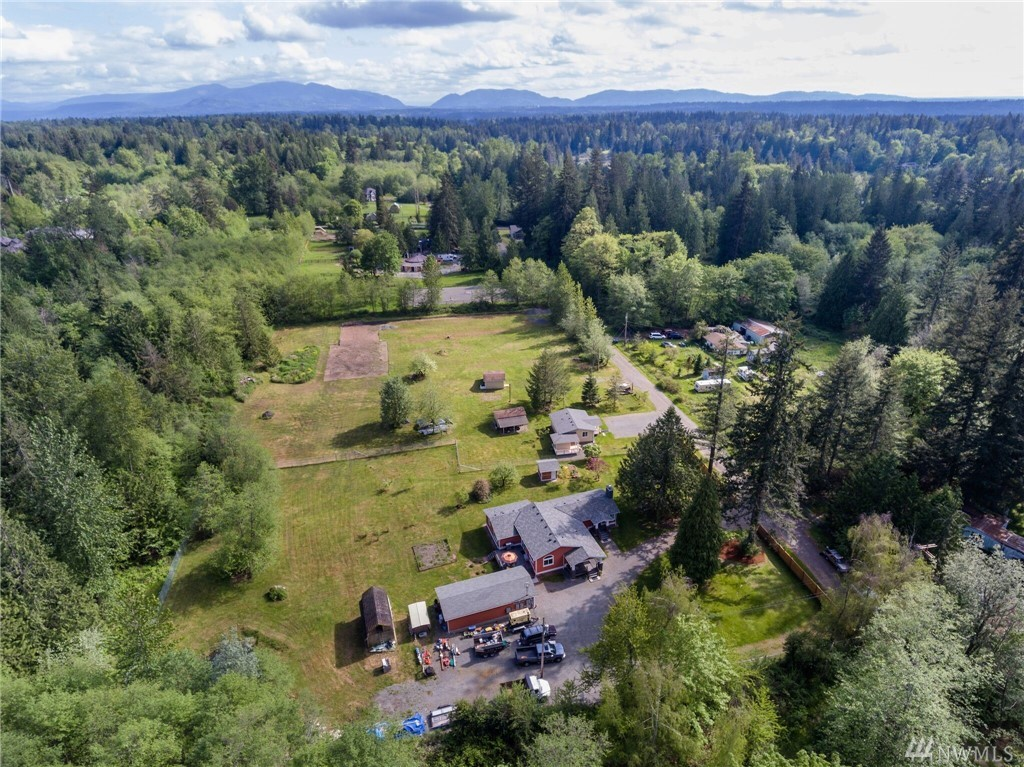 Two homes on one pristine equestrian 3.99 acres property w/existing shop & permit approved-to-build 80x50 shop/barn. Custom built home features a 50 yr roof, Hand-scraped hardwoods, top of the line finishes, beautiful Chefs kitchen w/high-end appliances & 10 ft ceilings, arched windows, granite counters w/island that flows out to large deck, great for entertaining. Second home is perfect for extended living or rental income & can be increased in size. Property is a Must See w/a lot of potential!