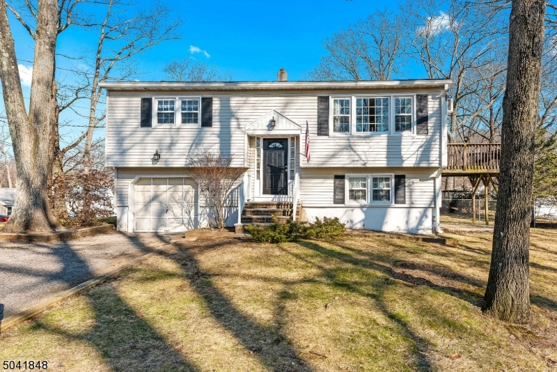 This fantastic home is ready for a quick close. Hardwood floors throughout, updated bathrooms, newer roof and windows make this a worry free home run. Step into this bright and sunny home, large picture window in the living room. The spacious kitchen is open into the dining room which has a slider out to the contained deck. Down the hall you will find 2 bedrooms and an updated bathroom . The lower level has the 3rd bedroom, family room with sliders out to the patio and a large, updated full bath with washer and dryer. The extra deep garage has access to boiler room and space for a workshop. Tucked away on a quiet side street, just off Mt Arlington Blvd, this corner lot has large flat yard space and is super close to the Shore Hills Beach and Nixon school
