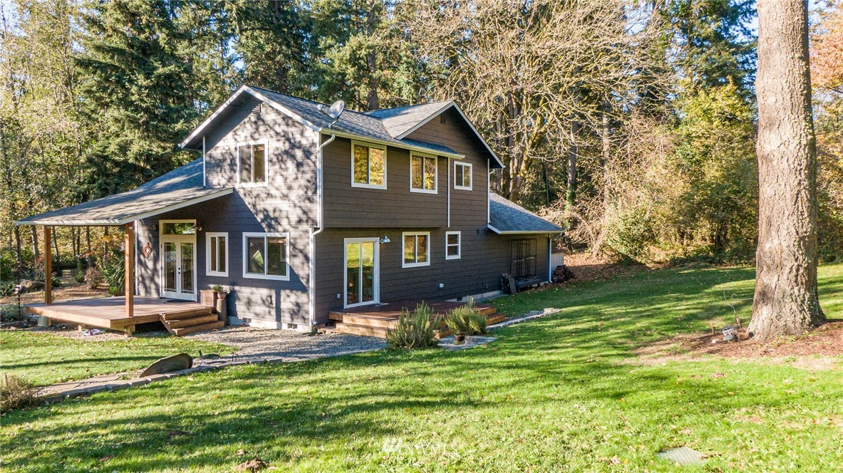 A parklike setting for the orchard, gardens, and versatile outbuildings surrounding this turnkey, appealing NW contemporary! Beautifully maintained, the 3 bedroom, 2 1/2 bath mini-farm is located within minutes of town and schools, yet surprisingly private at the end of the lane. Covered porches make inviting outdoor rooms. Septic design for 4 bedrooms. Additional refrigerator included in the sale with generator, mower, rototiller. Room to move!