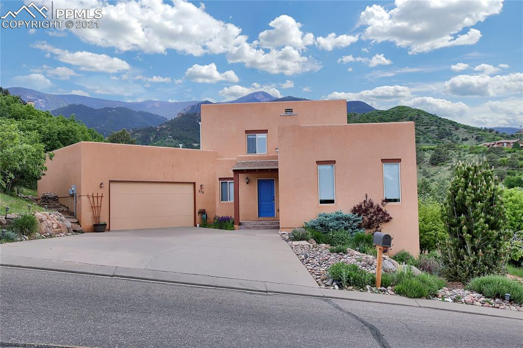 The beauty of the southwest is captured in this stunning home in desirable Crystal Hills. Magnificent views of Garden of the Gods and the surrounding mountains from the abundant decking, and through each strategically placed window. This home is fresh and contemporary with a peaceful, open flow. There are 3 baths and 4 spacious bedrooms plus a loft and an office space. Focal point fireplace in the living room. Gorgeous kitchen with maple cabinets, stainless steel appliances & large pantry. Great Garden of the Gods and Pikes Peak view from walkout deck! There is a large laundry/mudroom with a utility sink off the garage. Underneath the interior stairs, you will find an adorable miniature nook, a fun play area. Huge master bedroom suite with lovely master bath and walk-out to deck. Attractive knotty Douglas fir wood flooring, custom lighting. Exposed viga beams in the separate dining room. Oversized 2-car garage. The 0.25 acre lot is xeriscaped and natural with beautiful perennial flowers. Located close to the school bus stop and a quick walk or bike ride to local shops and restaurants.
