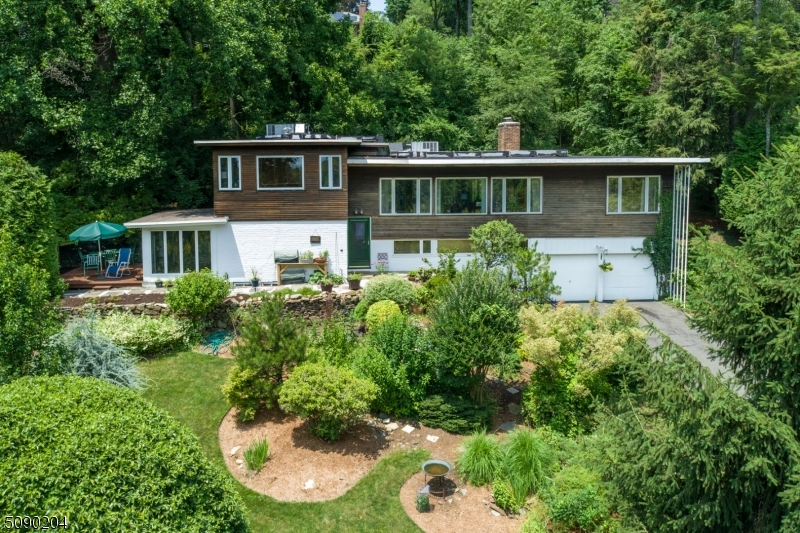 Mid-century Modern Treasure in Mountainside! Feel away from it all in this architectural gem nestled on private lane next to Watchung Reservation. Designed by renowned architect Kenneth Kassler. PRIVATE 1 Acre w/ seasonal NYC views. This home hallmarks clean lines, built-ins, high ceilings, open spaces & tons of windows. Orig details such as Built In Desks, Orig Railings, prolific use of wood including Orig Wood Plank Walls throughout, Built In Closets & Built In Open Shelving. Open & airy LR w/ mod recessed FP & breathtaking views. Updated Kitch, Gracious DR, Sunroom, & Spacious FR. Private & airy PMBDS w/ BuiltIn Closets & stylish bath. Side Deck & Rear Patio are nature lovers dream. Express Bus to NYC, close to shopping & restaurants. LOW Mountainside taxes! Don't miss this architectural masterpiece!