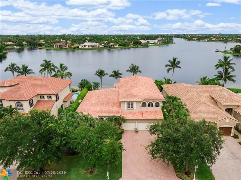 Premium lake lot with million dollar views of Lake Coral Springs!! This beautifully maintained home is located in one of Coral Springs most sought after gated communities! Features include a glass door foyer entrance, formal living & dining rooms, breakfast area, family room, a spacious loft, tile & hardwood flooring, built-ins, accordion shutters & impact glass! The kitchen offers cherry wood cabinets, center island, double ovens, granite counters & pantry! The master suite has his & her closets, sitting area, his & her vanities, walk-in shower, roman tub & bidet! Entertain family & friends in your own backyard paradise! Tropical landscaping, fenced and heated pool & spa & a huge brick paver patio! Great location & stunning wide water views! This is South Florida living at it's best!