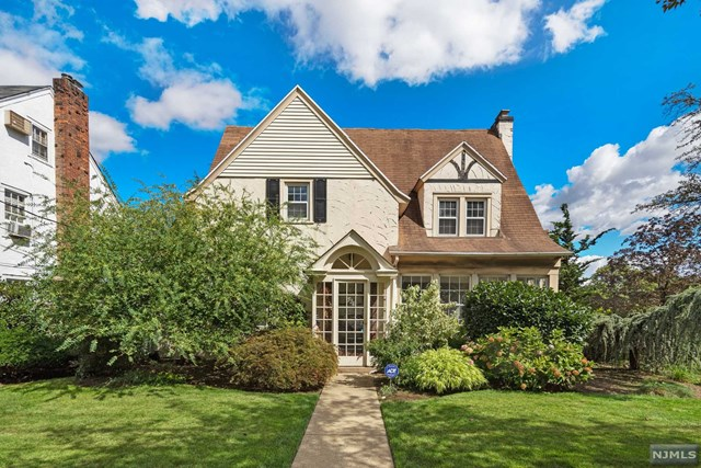 Super Charming Tudor colonial on prestigious Summit Ave! First floor boasts large living room with fireplace open to sunroom/sitting room with tons of windows and natural light, formal dining room with built ins, kitchen with updated appliances and powder room. Step down to bonus family room or private home office off of living room. Three large bedrooms with closets galore and hardwood floors and full bath on the second floor. Third floor features fourth bedroom and additional full bathroom--perfect for teen suite, playroom, home office, etc. Private rear patio, hardwood floors throughout, central air, masonry stucco exterior, large unfinished basement, new sewer line, updated 200 amp electric, in-ground sprinkler system, security system with cameras, and many updates!