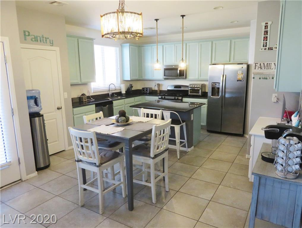 Located in the heart of Providence, this lovely home is in a gated community with a community park. Close to schools, services and the 215. Hard to find corner lot next to green space and extra street parking. This newer home has an open floorplan with many features like granite kitchen counters, two kitchen pantries, stainless kitchen appliances including refrigerator, contemporary painted cabinetry, updated custom light fixtures and new family room ceiling fan. The large master suite has THREE closets with separate shower and soaking tub. Convenient upstairs laundry room is adjacent to loft area. Recently updated family room laminate flooring with ceramic in the kitchen and baths and carpeted bedrooms. The backyard is completely shaded in the afternoons/evenings and features a large patio with artificial turf and side yard access is completely paved. Bring your grill and you've got the perfect outdoor entertainment space! This one won't last long.