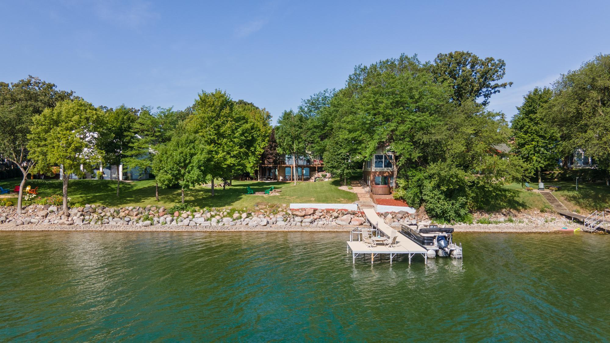 Spectacular Green Lake home offers rare, private 125' of lakeshore frontage. This house is loaded with unique features and great for entertaining! Open floor plan features remodeled kitchen with new appliances, granite countertops, and center island that opens to dining and living area with 3-sided stone surrounded fireplace. Features include main floor and upper level master suite plus three additional bedrooms. Enjoy the lake breeze and starry nights in the lakeside screen porch with gas fireplace! Lower level spa and low maintenance indoor pool with waterfall feature. The lower level features a large gaming and exercise area, second kitchen, and family room. Enjoy the spectacular lake views from every room. This home is professionally landscaped with boulders granite, mature trees, and fire pit. Maybe the best feature of this property is the guest house on the waters edge with full bath, kitchen, living room and storage. Located near restaurants, park,s and local entertainment!
