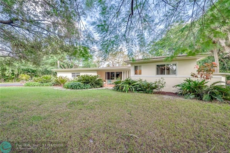 Wow! 30,000 sq. ft. (2/3 acre) of property when you factor in the backyard easement along canal. This property is like having your own private Nature Preserve with it's assortment of mature Oak, Cypress, Palms, Royal Poinciana, Mango, Ferns & more. The driveway holds 10+ cars + 2 1/2 car garage, roof 2014. Enjoy the Florida lifestyle with your own 608 sq. ft. screened back patio, hot tub included!. Two a/c's 2014 & 2016. Fenced back yard. Interior features terrazzo & Oak hardwood floors, crown molding, impact windows, split floor plan, inside laundry room, 2nd Bedroom should be consider as a second Master Bedroom with it own ensuite Bathroom.