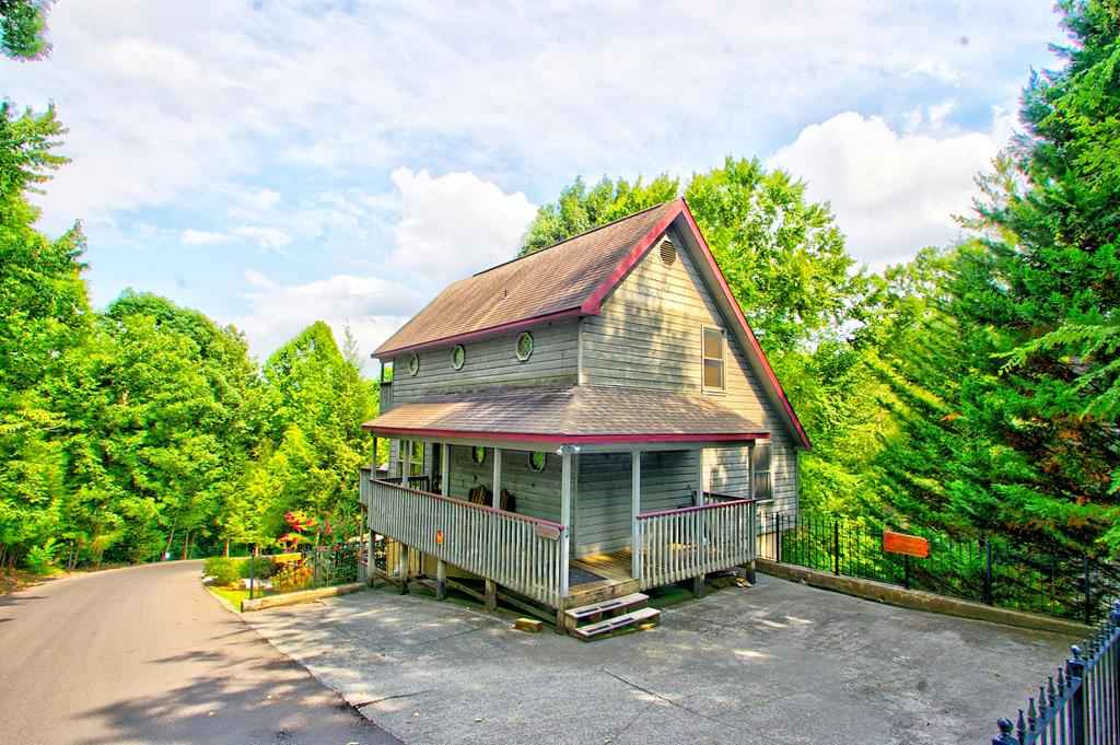 Here is a chance to own a cabin within a mile of the parkway in Pigeon Forge with all city utilities, and no steep roads. Woodridge Village has low HOA fees that pay for water, sewer and two community pools. This property can be rented on a short term rental program or used as a second home (which is what the current sellers have done). The sellers had this home built by the original developer and had first choice of lots in Woodridge Village. The one they chose is directly above the swimming pool and picnic area (literally 50 feet away.) You and your guests can walk to the pool in less than a minute. The home was used as a second home by the sellers for approximately 2 months out of the year, and was remodeled recently, with granite countertops in kitchen and all baths, hardwood floors in the great room. Stainless Appliances have very little wear and tear. as well as the included furniture. Central heat and air  consists of 3 individual York, high end heat pumps. Perfect privacy with a master on the main, a bed and bath downstairs along with what can be a great game room with wet bar, wine cooler and deck which include a hot tub and view of the pool. Two bedrooms upstairs are separated by the common bathroom with a balcony overlooking the pool. The living room has plenty of light with a skylight and gable window for an airy feel. Also in the living room is a floor to ceiling stone fireplace with a natural gas log kit.                                 This one is ready for the rental program for a profitable investment or make it your private getaway in the Smokies.
