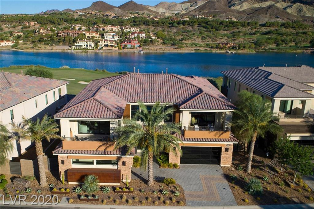 Waterfront in Lake Las Vegas, this former model home by William Lyons boasts unparalleled luxury. Stunning lake and golf course views. Natural light throughout. 3 bed/5 bath, bar, contemporary finishes. Large double height living room allows for indoor-outdoor living with pocket doors. The master suite offers a multi head shower, elegantly designed bathtub, and a covered patio. Spacious backyard with pool, spa, fire lounge & dining area. Exclusive private beach with cabanas for residents.