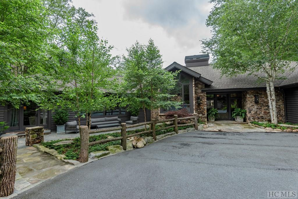 "A unique one-of-a-kind property (+/- 3.6 acres) in beautiful Highlands Falls Country Club.  Feel your blood pressure drop as you enter the grounds.  Positioned alongside Salt Rock Creek, this beautifully appointed high-design (with rustic touches) residence displays equal portions of magnificence both inside and out.  The Main Floor has it all, replete with a Master Bedroom Suite separated at one end for privacy.  Follow the high ceilings and fully-windowed interiors to an open-plan chef's kitchen.  From the custom imported Greek counter-tops of the kitchen, you'll serve party guests and family in the surrounding living areas as they gather around 2 interior fireplaces.  The Lower Level boasts 3 guest suites flanking a multi-faceted media-library-gaming area. All living spaces ""walk-out"" to the great outdoors!  Head outside, where every outdoor living area has it's own custom stone built-wood-burning fire pit/hearth.  Continuing with the ""outdoor living"" areas, stroll to the stream-side sanctuary and lounge, perfect for reading, reflection or an afternoon nap just above the waterfall.  The sounds falling waters is the music of this property.  An ""Elegant Tree House"" is how some describe it.  A word about Highlands Falls Country Club (membership optional, but well-advised)...perhaps the most family-friendly and inclusive club on the plateau.  Golfers describe it this way; ""it may not be the longest course on the Plateau, but it's certainly the most beautiful course"".  Social membership includes everything but golf, and the most spectacular gym, fitness-class, workout facility in town.  Highlands, NC offers you the ""Aspen of the East"" experience. This town has it all...shopping, fine restaurants, artistic assets, theatre, music, and festivals. Fresh cool air abounds because we live in a temperate rainforest. Outdoor Life...it's everywhere you go. Come for a visit, stay for life!"
