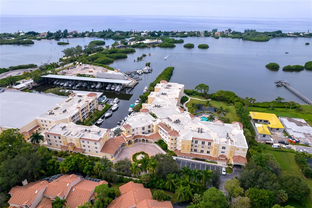 Live where the dolphins and manatees play. Luxury condo with spectacular views of the Intracoastal Waterway. Stroll to Casey Key and walk the beach, launch your kayak onsite and explore the bay. Walk to the Tiki bar across the swing bridge at Casey Key Fish house. This luxury condo has been beautifully updated in 2020. Brand new walk in shower in the owner's bath, with serene tile and new cabinetry and sinks create a spa-like experience. New expansive kitchen island with roll out storage creates a great cooking and entertaining space. New refrigerator, microwave, range, washer and dryer (2021).  New AC unit installed March 2021. The grounds and resort style amenities at Osprey Harbor Village are immaculate and curated with care. Bayside pool, club house, work out facility, jacuzzi and Sauna included onsite. Floating dock and fishing pier allow you the opportunity to enjoy your bayside location.  Have a boat or want one?, there are two marinas and a public boat launch right next door. Wet and dry slips are available for boating enthusiasts. Pet friendly complex, owners able to have two pets with no weight restriction.  Great storage available for a condo. California closets throughout and an interior utility room with laundry sink provide efficient use of space. Two under building assigned parking spaces and locked storage unit included as well as bike storage.  Osprey is uniquely situated between Sarasota and Venice.  Enjoy all that Sarasota County has to offer and embrace waterside living at its best!