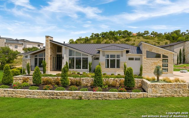 Sophisticated elegance in the Texas Hill Country.  One story 2017 Parade Home is sure to wow with exquisite finishes and fine details. The grand entry opens to soaring ceilings, gorgeous views and an abundance of natural light.  Sleek chef's kitchen features a striking waterfall island that also acts as a bar. The custom cabinetry is accented by a herringbone backsplash, stainless steel appliances and a professional gas range.  Tranquility and privacy are found outdoors with a large covered patio and a built-in gas grill perfect for entertaining. The lot is very level and would easily accommodate a pool.  The master retreat has a large walk through shower, dual shower heads, his and hers sink areas and an extra spacious closet.  The three secondary bedrooms are split from the master suite. Oversized three car garage with contemporary glass/aluminum doors.  Features also include: a wetbar that serves as a focal point in the dining room,  gorgeous ceiling and lighting detail throughout, custom sliding glass door in family room, an abundance of  storage, extra large laundry with custom cabinetry, built-ins in the study, mudroom bench, new metal roof (2019), floor to ceiling fireplace and mature landscape