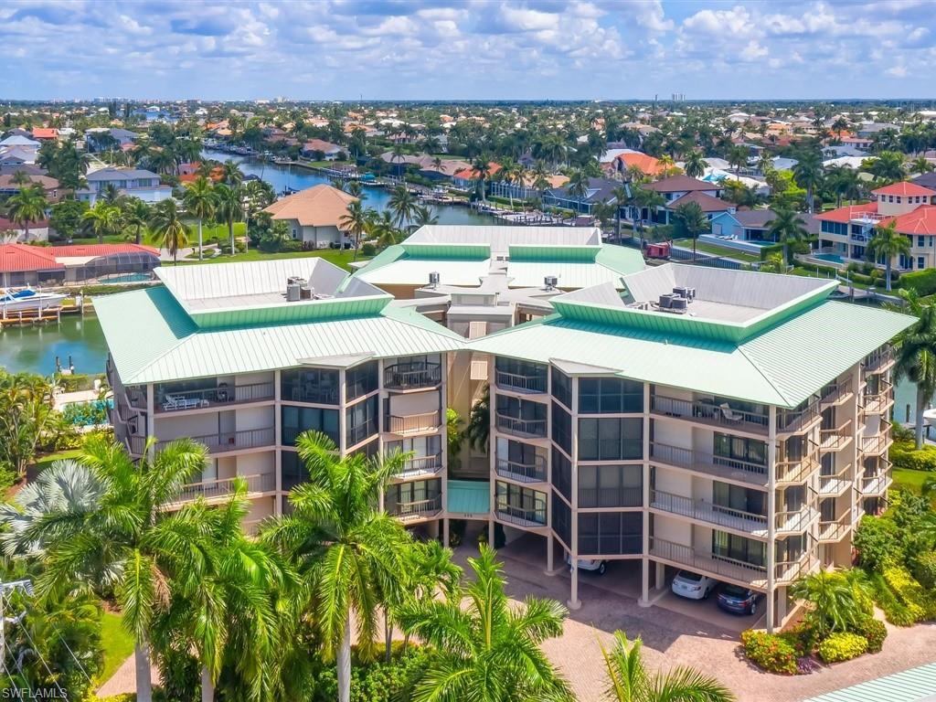 LOCATED IN LESS THAN 1 MILE TO SOUTH BEACH and DIRECT GULF ACCESS! Expertly remodeled in 2019 from top to bottom, this casually coastal FULLY FURNISHED 2 bedroom, 2.5 bath, 1,660 sq. Ft. 4th floor unit with a boat dock and 16,000# lift affords all the features of a single family home with the convenience of condo living! You will notice fabulous water views from every room complimented by the finest finishes and touches throughout the property from the moment you enter into the reconfigured open floor plan offering a generous living area including a gorgeous new custom kitchen featuring sleek flat panel cabinet doors, quartz counter tops, a massive breakfast bar with built-in cook top, built-in refrigerator, wall oven and microwave. Beautiful porcelain wood-look plank tiles, recessed lighting and remote control shades dress the space. The comfortable primary bedroom offers a stunning en' suite bath while your guests will enjoy a spacious bedroom and a wonderfully updated bath. Renovations include new wiring and panel box, all plumbing lines, AC, hot water heater and boat lift, all new appliances including washer and dryer. One under building parking space and storage unit convey.
