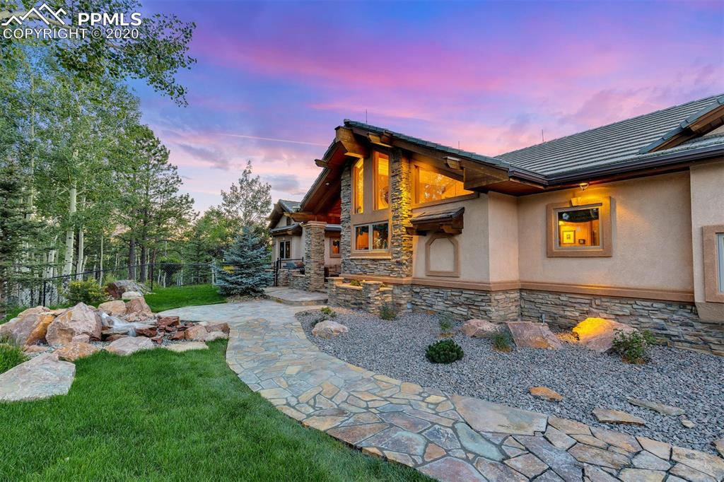 """A true custom creation, this mountain contemporary masterpiece was proudly featured in the Parade of Homes and no detail or feature was spared. Set on 6+ private acres, the Pikes Peak and mountain views are pure Colorado, and the proximity to countless recreation opportunities will astound. Refinished wood flooring and new high-end carpet flow from room to room, and in the kitchen, the bamboo and granite surface is a sight to behold. A true home theater with a 110"""" screen, full bar with impressive stone, and a spacious wine cellar featuring a hand-painted mural highlight the lower level entertaining space. The master bedroom and bathroom have a truly luxurious feel, with a double-sided fireplace, soaking tub, large walk-in shower, spacious closet, and a private balcony. The secondary bedrooms are large and each has a unique design of their own. The main-floor study is warm and inviting, and the home is equipped with 5G Wi-Fi via an owned tower on the property. The spacious front patio with gas fire pit and waterfall, all new landscaping, dramatic entry gate, new concrete pad at garage (with epoxy floor), asphalt driveway, concrete tile roof, and all new ironwood decks round out the incredible exterior features of the home. Set among a grove of stunning aspens and pine trees, wildlife of all kinds will also excite. Located just 10 minutes from downtown Woodland Park, 40 minutes from the Colorado Springs airport, 2 hours to Denver International Airport or Breckenridge, the home is a perfect getaway or year-round residence. This property is like nothing on the market today."""