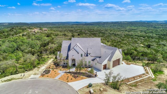 """A contemporary French country estate perfectly positioned, overlooking the expansive Texas countryside. With a blend of Old World & contemporary architectural styles, this unique home features breathtaking views, exquisite design details, rustic elegance, and refined comfort. Brilliantly designed, almost-new home on over 1/2 acres (with option to own neighboring lot) features a durable stucco and hand-cut limestone exterior, slate-style concrete tile roof, fully xeriscape landscaping with striking butter stick terracing. From every room, care was taken to seamlessly blend indoor space with the outdoors. The home's first floor features the great room with a vaulted ceiling and authentic reclaimed beams used to create load-bearing trusses anchored by an impressive stone fireplace with marvelous views afforded by a wall of windows.  Additionally, the chef's kitchen includes double islands and sinks, Thermador side-by-side fridge/freezer, Viking range and dishwasher, Bertazzoni food warmer, Miele coffee maker, Scotsman """"Sonic"""" ice machine and built-in wine cooler. The shaker-style, custom cabinets from Michael Edwards, are nicely styled with stone countertops and a classic tiled backsplash. The oversized master bedroom suite is complete with fireplace, spacious bath with vaulted ceiling, his and expansive her closet fit for a queen, his and her vanities, soaking tub and seamless glass rain shower. In addition, a media room, secondary bedroom, pool bath and office round out the first floor. A staircase leads one upstairs which includes 2 en-suite bedrooms and a giant storage room. Enjoy every season through the custom collapsing doors from the great room into a screened terrace with living area, fireplace, and outdoor kitchen with Coyote grill and outdoor fridge. The negative edge pool features a hot tub, sun deck with bubbles, and fountain wall.  SPECIAL FEATURES:Premium cul-de-sac lot in the Canyons at Scenic Loop located on the edge of the neighborhood with no neighbo"""
