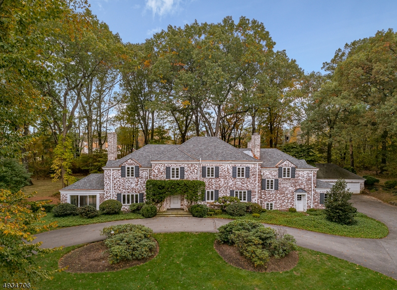 "Built in 1939, and situated on one of Harding Township's most scenic country roads, this 7 bedroom, 5.1 bath treasured Colonial, ""Acorn Hill"" offers a rare standard of elegance and prestige. With two stone pillars at the entrance, a long and winding paved driveway leads to the grand white-washed brick residence. The home features old world architectural features including wide curved staircases, arched-entrances, ornately-mantled fireplaces, intricate millwork, and custom windows. This residence sits on 6.27 acres of land that borders protected property and features oak trees and mature greenery.  Recent improvements include fresh paint, refinished wood floors, new roof with copper flashing  and a new 7 bedroom septic system."