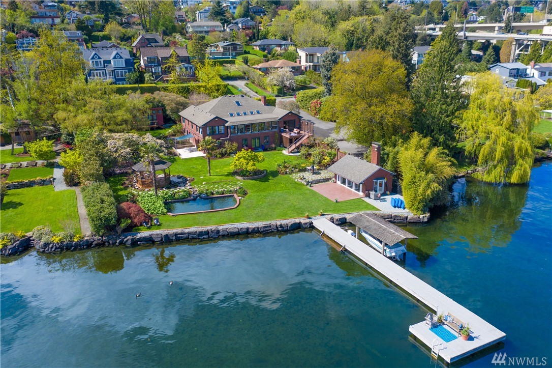 Private Lake Washington compound. Magnificent protected panoramic views framing Mount Rainier. 124-ft of shoreline: Versatile gathering spaces for enjoying sweeping lakefront gardens; beach cabana, creek, reflecting pool. 70-ft long premium dock. Lavish yet unpretentious venue for a casual BBQ, wedding, benefit concert or grand soiree. Ample guest quarters. Plentiful parking. Rich in Seattle lore, set in historic Seattle neighborhood served by light rail. Timeless sanctuary in a changing city.