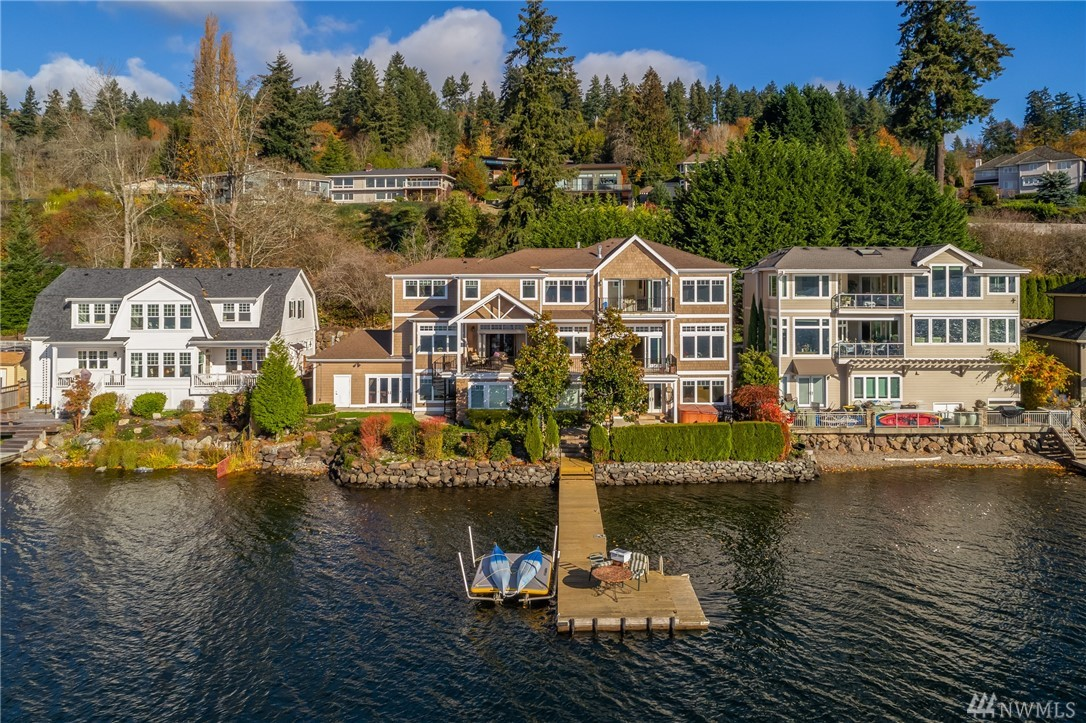 On the peaceful West shore of Lake Sammamish this rare estate offers 101 feet of low-bank waterfront with a private dock surrounded by lush gardens. Soaring 12 ft ceilings accentuate sparkling lake views from every vantage point. Designed to entertain; indoors and nature blend harmoniously on three levels with spacious outdoor terraces. Artisan kitchen, chiseled stone fireplaces; lower level wine cellar, gym, library. MIL/ rec room with 2nd kitchen. Epic sunsets! Minutes from dining & shopping.
