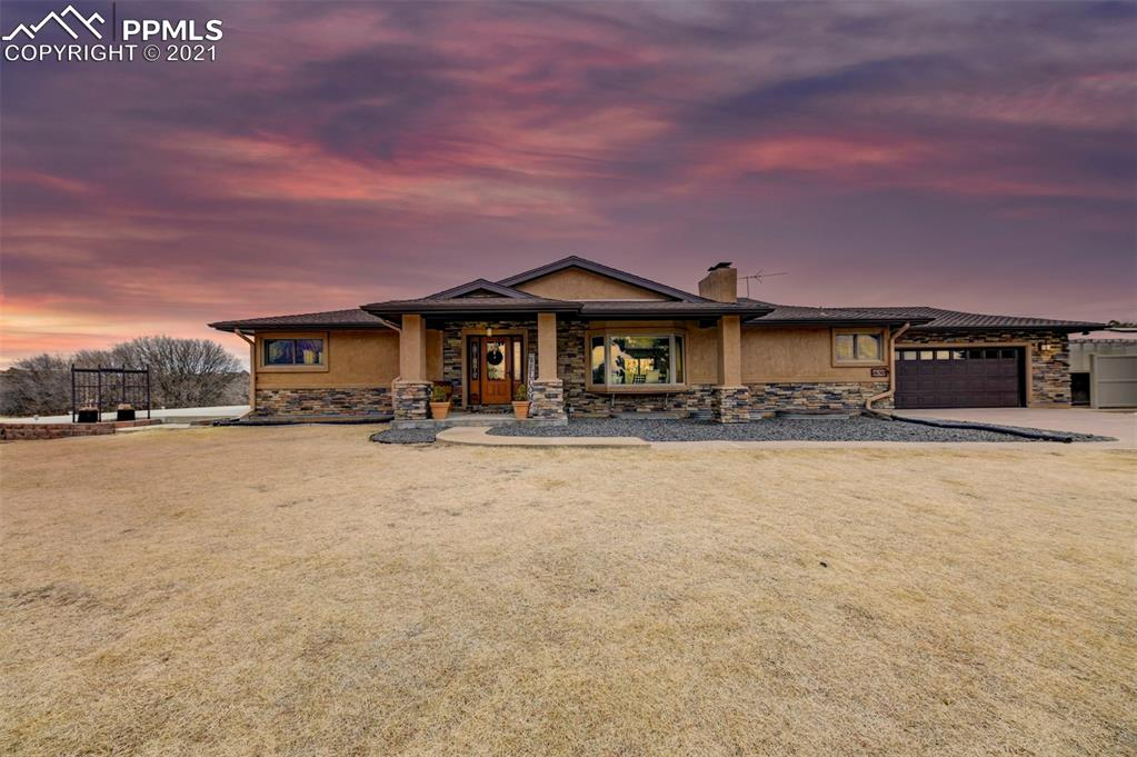 WELCOME HOME COLORADO This 2.5 acre rural oasis is nestled right in Colorado Springs! Just minutes from active city life, relax and take in the beautiful front range views. It's a RARE find in the desirable Spring Crest neighborhood! Inside, gleaming hardwood floors and a gorgeous, brick wood-burning fireplace, welcome you. Off the living room, you'll find an executive style home office with a private 1/2 bath. Indoor/outdoor dining options on a 12x18 terrace with pergola, right off the dining room! The kitchen boasts beautiful solid hickory cabinets, granite countertops, Swanstone sink, and all appliances are included. The spacious main level laundry includes a washer, dryer with drying cabinet, and built-in cabinetry with laundry sink. Main level master bedroom has French doors leading to stunning mountain views from a 25x25 patio, pre-wired for a hot tub! The upgraded master bath has a large walk-in closet, dual vanity, freestanding tub with waterfall faucet, and custom walk-in shower. Plus all windows on the main level have low E-glazing! In the basement, you'll find a huge family room with a second wood burning fireplace and fabulous ceramic tile flooring. A generous wet bar and entertaining area, and a home theater room complete with up lighting and speaker prewire. The basement level also includes 3 additional bedrooms with recessed lighting and built-in shelves, and a full bath. Outside the home, you will find a detached 750 SqFt workshop. Used for woodworking, it includes existing ductwork for a dust collection system. Also, a 12x24 greenhouse is a gardener's dream! Greenhouse features roof vents, a ventilation fan and planting tables. Even the garden shed has electricity! Split rail fencing surrounds the front and sides of the property, while natural Scrub Oak borders the rear. A privacy fence closer to the home helps to define the backyard space. Property is zoned for horses too! Come and see this beautiful gem and enjoy those mountain views!
