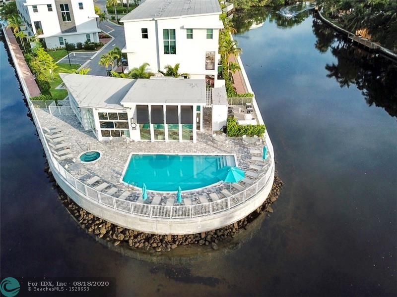 """TRANQUIL WATER VIEWS from this SOPHISTICATED Tri-level Townhome in the sought after riverfront community of The Pointe @ Middle River. Across the River from Wilton Manors, this ELEGANT home is full of luxurious upgrades (OVER 60K)! Custom Italian Porcelain floors complemented by rich hardwood staircases set the tone for European style. This MAGAZINE-LIKE home allows you to experience serenity while taking in the river views through an 18' slider leading to 1 of 3 balcony/terraces. Entertain and host gatherings in your open kitchen w/42"""" cabinets, quartz counters, SS apls, including a GAS range and double ovens. Stay dry with your 2 car garage. Community features only 40 homes, heated pool, hot tub, gym & clubhouse all over looking river. Walk to nightlife, Wilton Drive & DWTN Oakland Park!"""