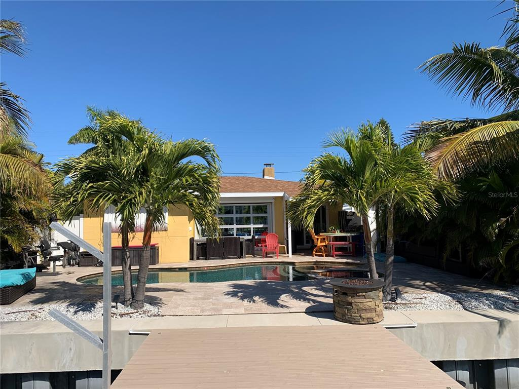 """When entering, the retro terrazzo floors and amazing pool and intracoastal views through the extra large patio door will undoubtedly make you say """"Im Home!"""" Since 2015, owner has installed a new ac system, an in ground pool/spa on the patio and a new taller seawall fronting the deep water sail boat access along with a new dock, floating dock and lifts to safely store your water toys! . What's the old saying?? Location, location, location as you will be in close proximity to the beach, bars and restaurants, Treasure Island Town Center and World Famous Johns Pass only minutes away. Like to go boating? Perfect! **  As a bonus, a 2015 23' pontoon boat, furnishings, 2 jet-skis, kayaks and paddleboards will be included in the sale as well as all appliances with acceptable offer  ** Not available to show until after 10/10/2021 but call today to set up a private showing..**"""