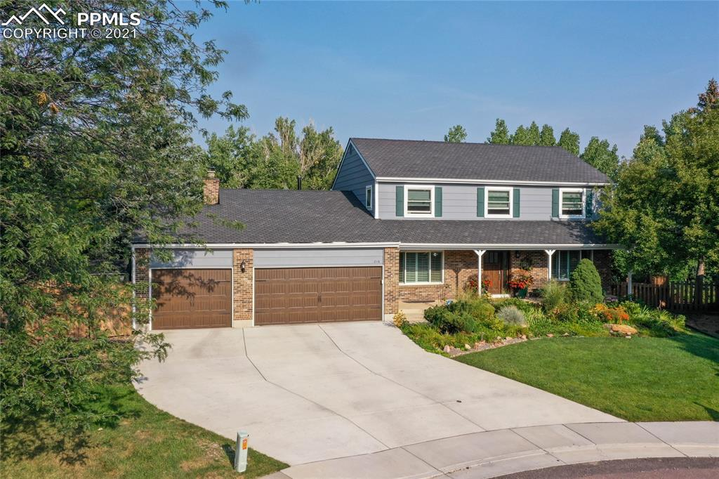 This stunning two-story, former model home sits among mature trees and landscaping on a nearly ½-acre lot within walking distance to Broadmoor Elementary School. The floorplan is versatile for entertaining yet comfortable for easy living. The main level includes both a formal living room and family room with gas fireplace, built-ins, wet bar and walk out to a massive 67-foot composite deck with retractable awning and additional covered area. No expense was spared in the newly designed gourmet eat-in kitchen featuring Crystal Cabinets, Thermador appliances and Quartzite counters. The on-trend color scheme and matte gold hardware complete the package. You'll also enjoy the convenience of having the laundry off the kitchen and two large pantries. A half-bath and formal dining room round out the main level. The upper level features a large master suite with state-of-the-art walk-in closet plus three more bedrooms and full bath with jacuzzi tub and double vanity. The basement provides more entertaining options with a family room that walks out to a patio, wet bar with freezer and microwave, and an additional bedroom and bath plus storage. The pool table and perfectly sized sectional come with the house. Located in a cul de sac, this beautifully landscaped property features a perennial garden in the front and large Blue Spruce, pines and Cottonwood trees in the rear backing up to a creek. The setting is serene but also provides plenty of space for outdoor sports and activities. The 3-car garage with epoxy floor offers plenty of storage with built in cabinets. Located in the award-winning Cheyenne Mountain School District and minutes from both The Broadmoor and Country Club of Colorado plus easy access to I-25 and the Highway 115 corridor.