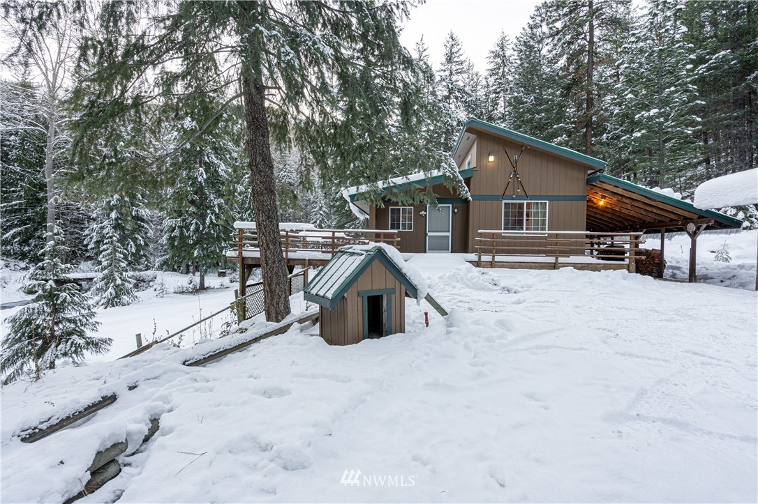 Your recreational paradise awaits in this great 2 plus bedroom cabin on ten acres near the Sno Park with 430 ft. of Gold Creek frontage. Bring your toys, your cross country skis or snowmobiles to this winter wonderland. Cozy up to the wood stove and enjoy the serenity from your wrap around deck year around. The vaulted ceiling lets the sun shine in thru the pines. A two car detached garage with a carport and living space above and another guest cabin with a carport offers endless growth potential. Two wells, a hot tub and a bridge over Gold Creek to the additional acreage makes this a very special setting to enjoy in summer or winter.  Remodeled in 2010 with new flooring, kitchen, and windows. 2nd bedroom has a sleeping loft. Backs up to FS