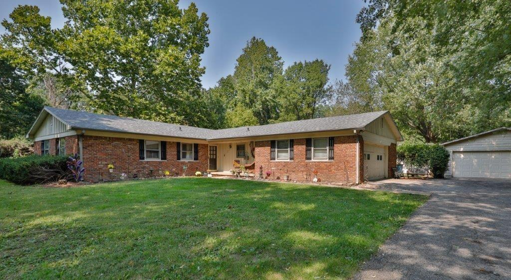 All Brick Ranch 4BR|2BA Home Nestled on over 3/4 acre + Additional .11 AC (See Agent To Agent Remarks)  FOUR-Car Garage. FRESHLY Painted Interior & NEW Flooring in both bathrooms. Tree Lined Lot offers you all the privacy you need. NO HOA. Open Floorplan Features a Large Kitchen w/Fireplace & Hearth RM, Vaulted Beamed Ceiling & Access to The Backyard. Generously Sized Family Room, Dining RM with Ample Natural Lighting. TWO Smaller Outbuildings. Sit back and enjoy all the tranquility and views nature has to offer on the large deck which overlooks the backyard. Conveniently Located Near Geist Reservoir with Easy Access to I-70 & Nearby Shopping & Dining.