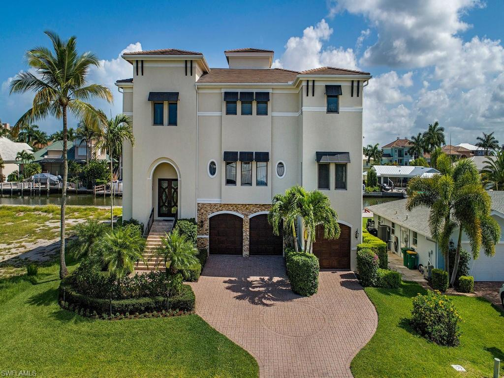This Conners waterfront estate has everything the discerning homebuyer can ask for.  Immaculately maintained and recently renovated to the highest of standards.  Open floor plan with natural sunlit rooms embrace you upon entry into the dramatic foyer with soaring 30 foot ceilings.  This house is perfect for entertaining guests with large open spaces, multiple outdoor and open balconies and a first floor game room, bar and entertaining area that spills out onto the lanai with your private pool and spa overlooking your covered boat dock resting on the canal.  This true tropical paradise embraces the Naples lifestyle of happy and healthy living. The kitchen has double island with waterfall countertops, custom wood cabinetry and oversized stainless side by side refrigerator and freezer.  The master suite has his/her closets with custom built mirror and glass cabinetry, a walk-out balcony and large open bathroom. There are 5 professionally decorated guest rooms boasting water vistas from every window. Conners at Vanderbilt Beach is  the Gold Standard for North Naples waterfront living located 1.5 miles to Vanderbilt Beach, provides quick Gulf of Mexico boating access.