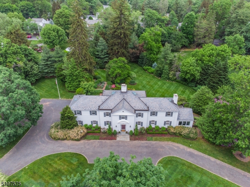 """Stunning, classic + gracious estate on 1.75 ac lot in prestigious Dellwood Park. Summer will never be more enjoyable than getting to take advantage of the gardens of this incredible home. The front of the house presents a wonderful expanse of classic brick colonial construction. Inside, a sweeping staircase overlooks foyer. An elegant LR offers panoramic views of terrace + French doors that lead to the sunroom with views of the """"secret garden"""". Den w/fireplace, built-ins + guest bath. Hall w/wine storage leads to kitchen and DR. Kitchen boasts a wall of windows +  access to laundry room and garage. Upstairs offers 5 BR/4BA, including beautiful Primary Suite+2 ensuite BRs. Unique LL w/ arcade, old-Hollywood-style movie room, + 50s diner gathering space w/ guest bath. Fantastic yard w/room for pool or expansion."""
