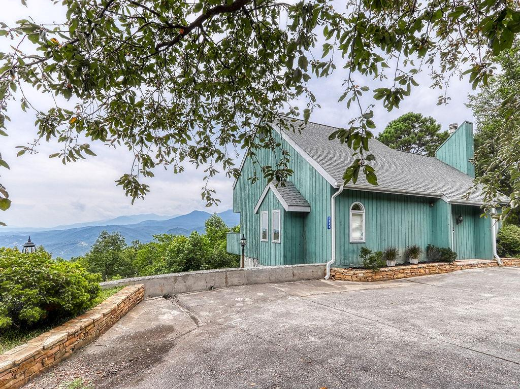 One of a kind Chalet with stunning panoramic views of the Smoky Mountains! Completely remodeled and updated this modern chalet is an absolute stunner! Enjoy beautiful mountain vistas from every room in the house with this spacious and open floor plan. On the main level you will find a large open living room with soaring vaulted ceilings and a wood burning stacked stone fireplace. There is a formal dining room right off the kitchen with tons of windows to let in the natural light and take in the gorgeous mountain views! The kitchen features new granite counters, stone backsplash, new stainless steel appliances, and a kitchen island with plenty of seating. Right off the kitchen you will find the master bedroom which has one of the best mountain views Gatlinburg has to offer! There is plenty of room for a king sized bedroom suite, and the fully updated bathroom is simply perfect. The french doors from the master lead out to the main level deck which extends the whole length of the house for plenty of outdoor space. Head upstairs and you will find a spacious loft area that could be utilized as a game room or additional living area. There are 2 additional bedrooms with sliding doors that lead to a second deck that allows you to take in those beautiful Mount Leconte views. Off the bedrooms there is another full bath that has been totally remodeled and includes a walk in tiled shower. This bright and airy chalet is everything you have been looking for, and is in one of the best locations Gatlinburg has to offer. There is plenty of level parking and only a 1 step entry into the home. Call today to schedule a showing or request a video walk through.