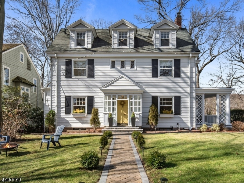Stunning & stately, this gorgeous Colonial is not only glowing w/ character & modern renovations, but is ideally located! Only 900 FEET to train to NYC & town w/ dining and shops at your fingertips! Beautiful inside & out this spacious & well laid out modern home with exquisite charm is what dreams are made of! Downstairs enjoy the open plan from the dining room to the bright French bistro style kitchen & full bathroom, making entertaining ideal! Expansive living room with grand fireplace opens to a spacious side porch. Upstairs find 4 large bedrooms & 2 full baths. The third floor will WOW you as a DREAM master suite! Graced with WIC, double vanities, soaking tub, separate shower, & huge bedroom. Finished basement is a perfect bonus space! Outside enjoy dining al fresco on custom patio!