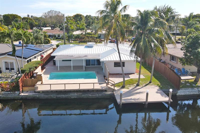 Do not miss this waterfront masterpiece just minutes by boat to the ocean! Be the envy of your friends and family as you show off the practically endless canal and poolside views just across the bridge from Wilton Manors. Boasting a brand-new metal roof, a grand kitchen with custom white cabinetry and high-end appliances, quartz countertops, impact windows and doors, ceramic tile throughout, 3 bedrooms, 2 fully renovated bathrooms, a laundry room and a massive family room in the front, your new luxury estate is completely rewired to today's standards. With a split bedroom floorplan and covered deck directly accessible from the master bedroom and living room, you and your guests will flow seamlessly from indoors to out, all the while retaining the privacy you long for.