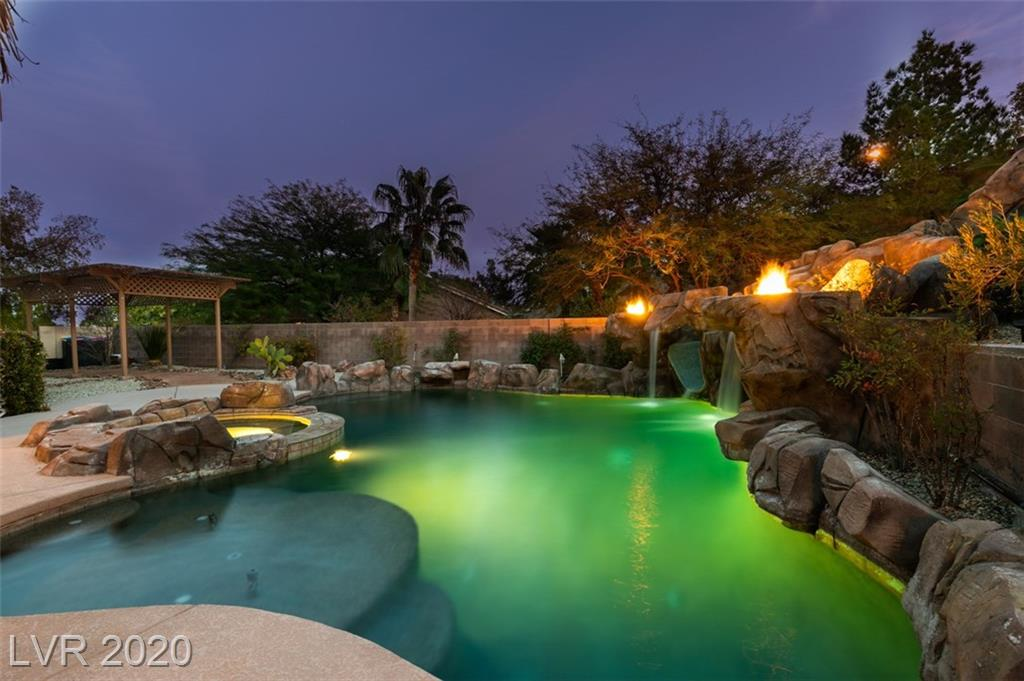 Fantastic single story home on a private 13,000 sq ft lot in the heart of Summerlin! Entertainers Paradise!!! Large Pebble Tec pool/spa with beach entry, waterfalls, slide, groto and fire features. Brick fireplace for your enjoyment, upper landing fire pit, Koi pond, putting green, outdoor kitchen with grill, sink, refrigerator and its own Tikki bar! Get tready to have a vacation in your own back yard! Second yard with private pad for your yoga mats or your lounging pleasure, all surrounded by rose bushes and fruit trees. You won't find another house with such incredible outdoor space! Bright and airy house with a huge master bedroom and separate sitting room with a custom designed walk in closet. Wood Plantation shutters and beautiful marble and synthetic wood floors throughout the house. Whole house Halo water treatment system. Large sun room with its own cooling and heating systems. Make an appointment to see this house today! You won't be disappointed!!!!